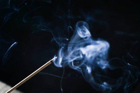 Photo pour Bâton aromatique fumant dans l'obscurité, fumée bleue - image libre de droit