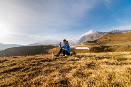 Photo pour Jeune fille active dans une veste bleue profitant de la nature et des montagnes du Caucase - image libre de droit