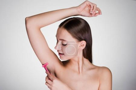 Young girl shaves her hair on her armpit with a ra...
