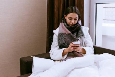 Photo pour Une jeune fille est couchée au lit avec un rattrapage froid avec quelqu'un au téléphone - image libre de droit