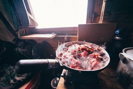 Photo pour Dîner de cuisine dans une cabane de chasse haut dans les montagnes - image libre de droit