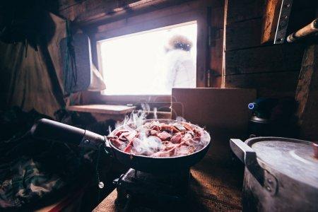 Photo pour Dans un pavillon de chasse dans une poêle à frire, la viande de cerf est rôtie - image libre de droit