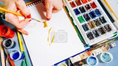 Foto de Mujer pintor pinturas sobre papel blanco con pincel y pinturas de acuarela brillantes - Imagen libre de derechos
