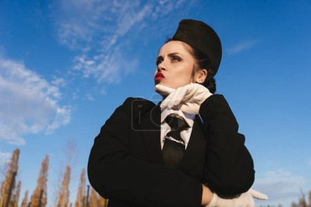funny young woman stewardess in uniform under a blue sky, thinking about airplanes