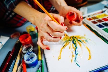Photo pour Femme artiste peint avec un pinceau et aquarelle brillante peintures sur papier blanc - image libre de droit