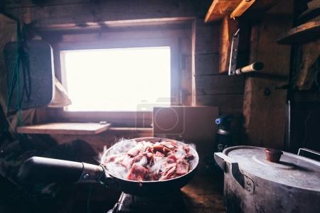 Photo pour Cuisiner de la nourriture en haute montagne dans une cabane de chasse - image libre de droit