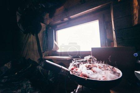 Photo pour Dans un pavillon de chasse dans une poêle rôtit de la viande de cerf - image libre de droit
