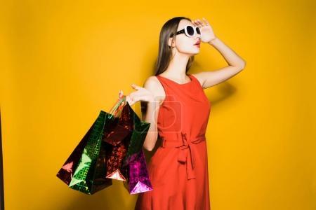 Photo pour Femme tenant des sacs à provisions et regardant loin - image libre de droit