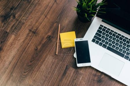 Photo pour Sur une table en bois est un ordinateur portable et téléphone - image libre de droit