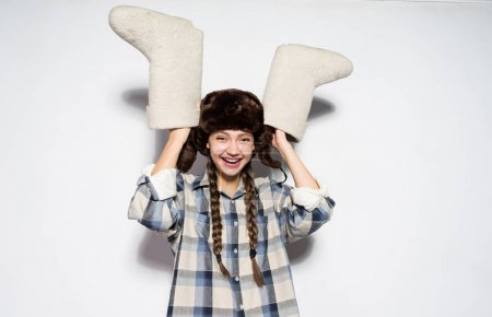 Photo for Happy Russian girl in a warm hat with ear-flaps holds gray felt boots in hands - Royalty Free Image