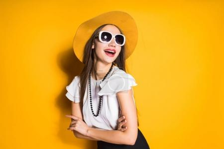 Photo for Beautiful stylish girl model in a trendy hat and sunglasses posing and laughing on a yellow background - Royalty Free Image