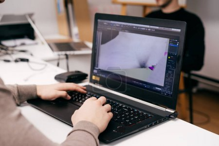 Photo for Male graphic designer working on laptop over project, office work - Royalty Free Image