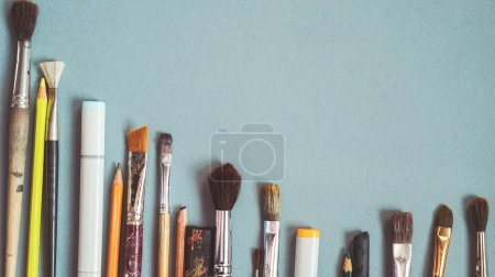 Photo for On a blue table are artistic brushes of different sizes, art - Royalty Free Image