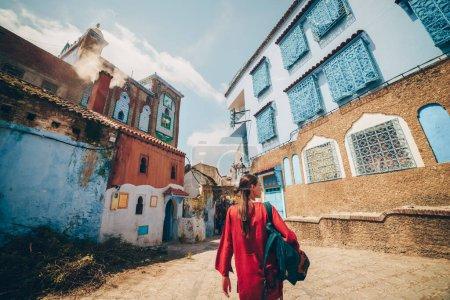 Photo pour Vue magnifique d'une fille marchant dans la rue dans la ville bleue de morocco vue de l'arrière - image libre de droit