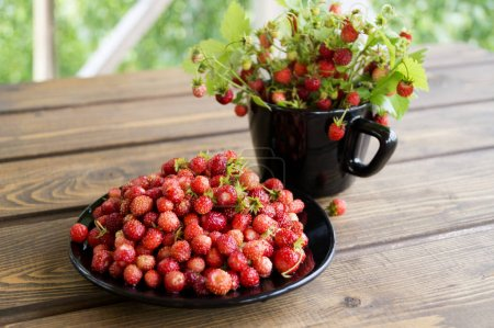 Strawberries in a white mug on a rustic wooden table. The concep