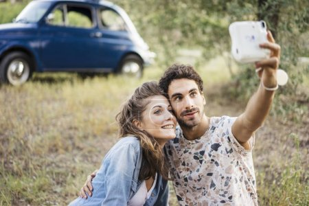 Couple taking selfie with instant camera