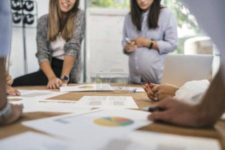 Creative people doing brainstorming meeting in mod...