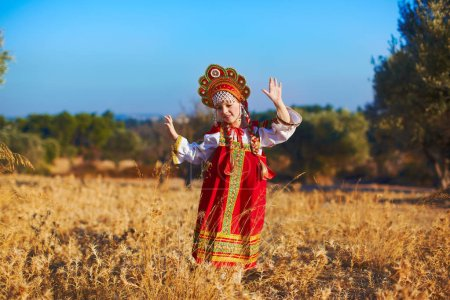 Photo for Beautiful girl in Russian folk costume dancing at field - Royalty Free Image