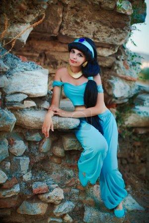 Photo pour Charmante jeune femme en costume oriental arabe sur fond de ruines antiques danse, sourire - image libre de droit
