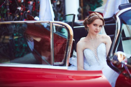 Beautiful  bride posing with vintage car