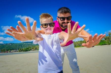 Photo pour L'enfance des plus heureuse: père et fils s'amuser sur la plage tropicale - image libre de droit