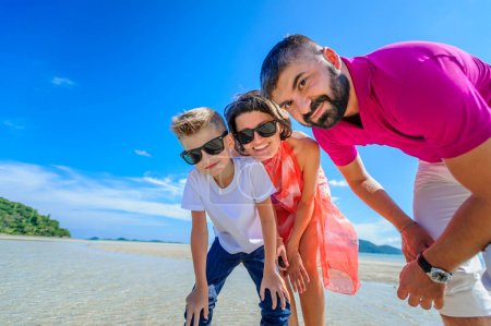 Photo for The happiest childhood: father, mother and son having fun on the tropical beach - Royalty Free Image