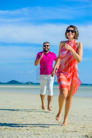 Photo for Happy married couple running and jumping along the tropical beach, laughing and enjoing time together - Royalty Free Image