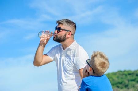 Foto de Retrato del padre bromas y no dando agua a su hijo guapo sediento en el desierto playa tropical - Imagen libre de derechos