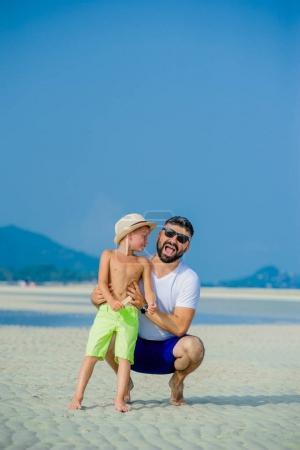 Photo pour Heureux jeune famille de trois personnes s'amuser sur la plage ensoleillée du désert - image libre de droit
