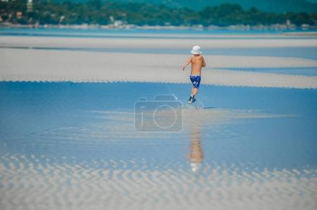Photo for Seven years old boy runnig along the desert sunny beach - Royalty Free Image