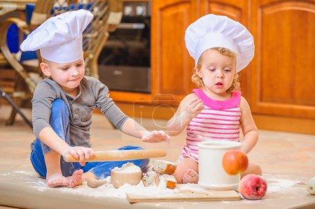 Photo pour Deux frères et sœurs - garçon et fille - de toques de près de la cheminée, assis sur le plancher de la cuisine sali avec de la farine, jouant avec la nourriture, faire désordre et s'amuser - image libre de droit