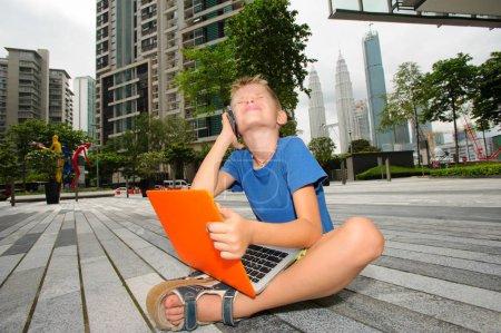Photo pour Mignon petit homme d'affaires au milieu d'une journée de travail. Vie de la mégapole. Travail sur ordinateur portable, assis sur la notion d'étage. Espace copie - image libre de droit