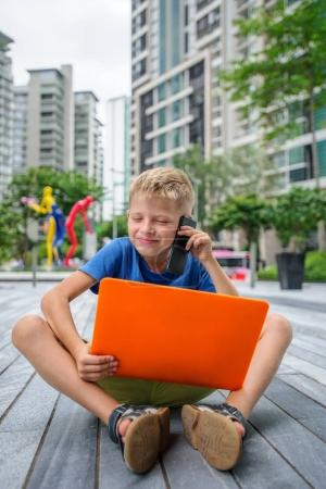 Photo for Cute little business man in the middle of a busy working day. Megapolis lifestyle. Working on laptop, sitting on floor concept. Copy space - Royalty Free Image