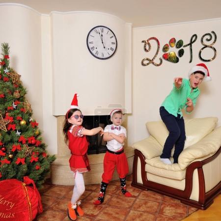 Photo pour Arbre de Noël et grand cadeau sac - jolie fille en costume rouge et de petites cornes, son cousin bleu eyed handsome, habillé en costume elf - grand frère dans le chapeau du père Noël. Analyses de chevreau et couchait - image libre de droit