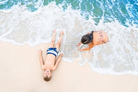 Foto de Lindo niño y una niña divirtiéndose en la soleada playa tropical. Tumbado en la arena, las olas maravillosas a su alrededor. Ve desde arriba - Imagen libre de derechos