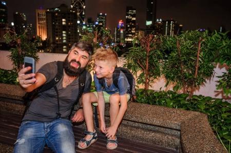 Foto de Mochileros en una gran ciudad. Padre e hijo felices y emocionado por el viaje de Malasia. Ciudad por la noche. Los rascacielos sobre el fondo. Vista desde una colina - Imagen libre de derechos