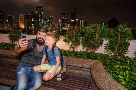 Photo for Backpackers in a big city. Father and son happy and excited together for the Malaysia trip. City by night. The skyscrapers against the background. View from a hill - Royalty Free Image