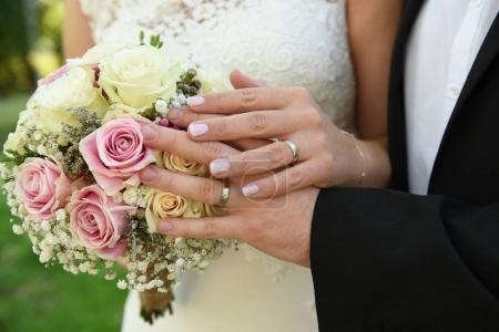 Photo pour Gros plan des mains de l'homme et de la femme avec des alliances et un bouquet de roses - image libre de droit