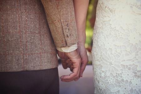 Photo pour Vient d'épouser couple tenant leurs mains, vue arrière - image libre de droit