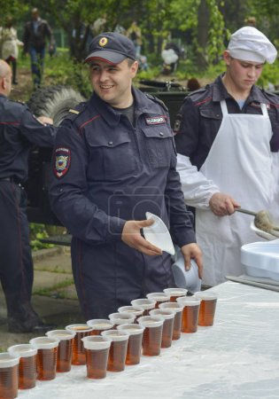 PYATIGORSK, RUSSIA - MAY 09, 2017: The employee of the Police distributes tea and food Movable white kitchen