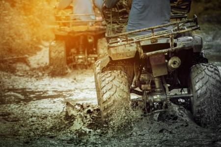 action shot of sport atv vehicle running in mud track