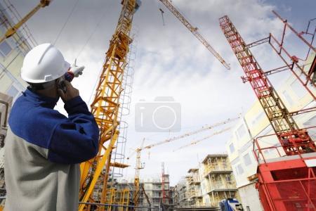Photo pour Travailleur de la construction pointant vers un grand chantier, grues et échafaudages - image libre de droit