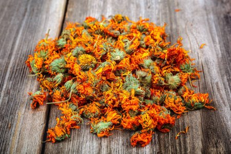 Dried calendula flowers on wooden background. Medi...