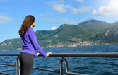 Beautiful girl looking lake and mountains sunny landscape on background outdoor. Travel healthy lifestyle concept.