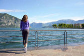Beautiful girl looking lake and mountains, sunny landscape background outdoor. Travel lifestyle concept.