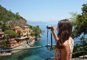 Back side of young woman taking picture of beautiful italian bay in Portofino, happy travel to Europe, summer vacation concept