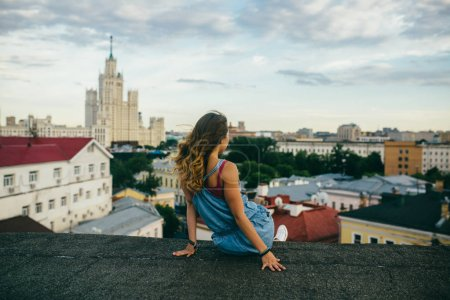 Rear view of blonde woman sitting on building roof and looking on cityscape at daytime