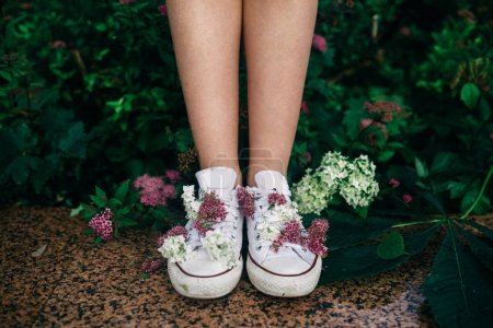 looking down view of female legs in gym shoes with flowers decoration