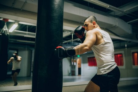 Side view of boxer training punch on punch ball in sport gym