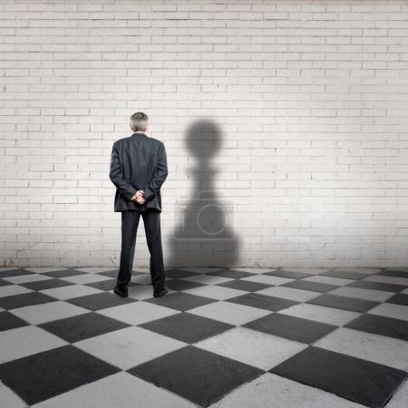 businessman with pawn shadow